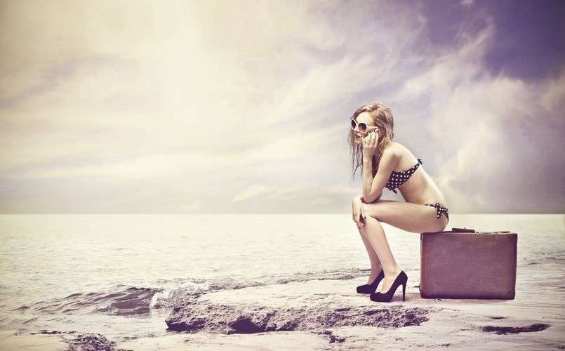 17546753 - beautiful girl sitting on a suitcase in the desert