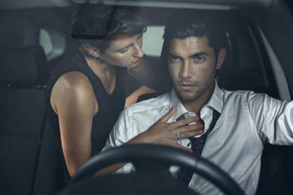 42149567 - beautiful woman on car backseat seduces driver. fashion and sensual