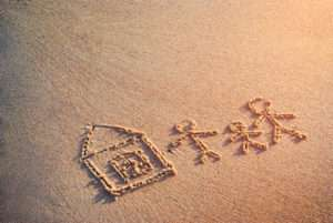 43421146 - family of three people with little house drawn in the sand of sea beach