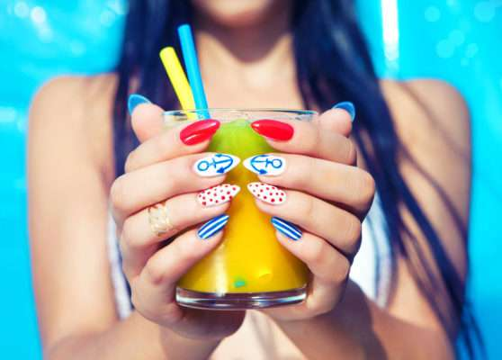 43150889 - young woman with marine sailor manicure holding glass of orange juice, summer nail art beauty and drink concept