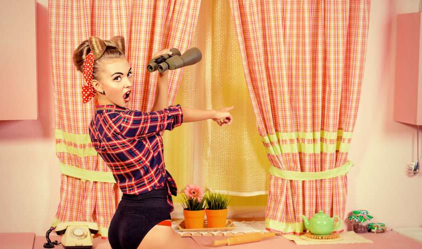 48504274 - lovely pin-up girl stands on a pink kitchen and through binoculars. retro style. fashion.