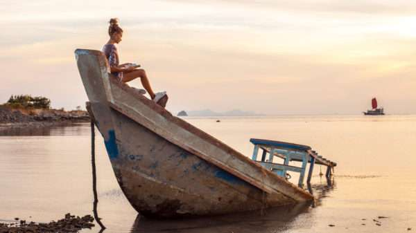 56567383 - young woman is sitting on the shipwreck and reading a book. tropical sunset on the background.