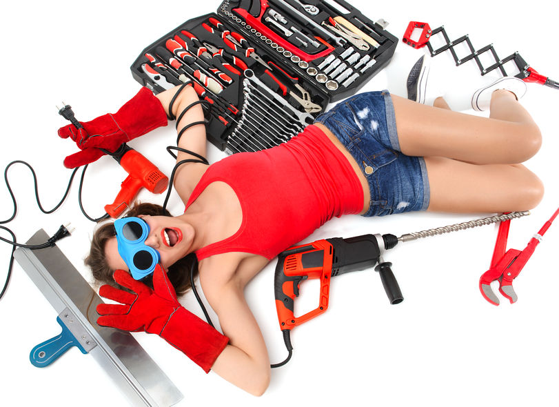 40218067 - happy sexy young woman contructor worker lying on a floor with construction set of tools wranches pliers drill spatula on a white background